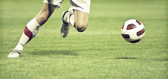 Football player running after ball